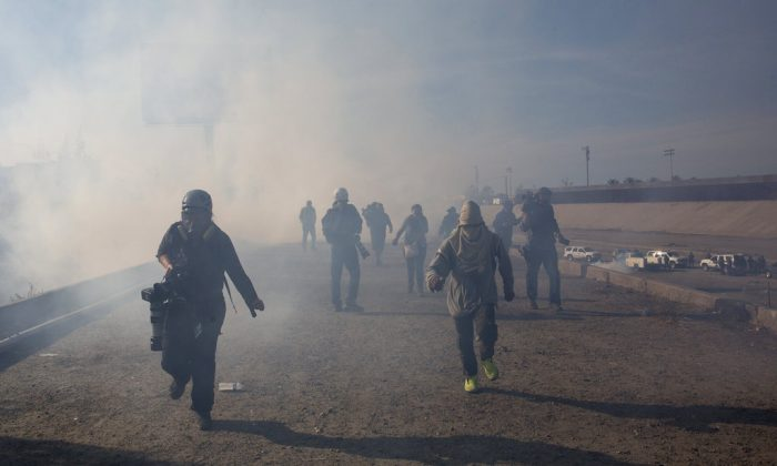 Migrants run from tear gas launched by U.S. agents, amid photojournalists covering the Mexico-U.S. border, after a group of migrants got past Mexican police at the Chaparral crossing in Tijuana, Mexico, on Nov. 25, 2018. (AP Photo/Rodrigo Abd)