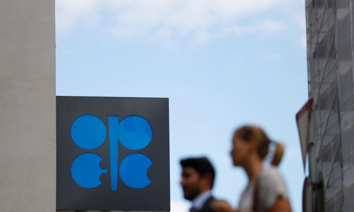 Two persons pass the logo of the Organization of the Petroleoum Exporting Countries (OPEC) in front of OPEC's headquarters in Vienna, Austria June 19, 2018.   (Leonhard Foeger/Reuters)