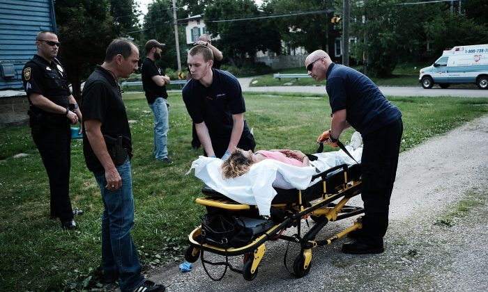 Medical workers and police treat a woman who has overdosed on heroin, the second case in a matter of minutes in Warren, Ohio,  on July 14, 2017. (Spencer Platt/Getty Images)