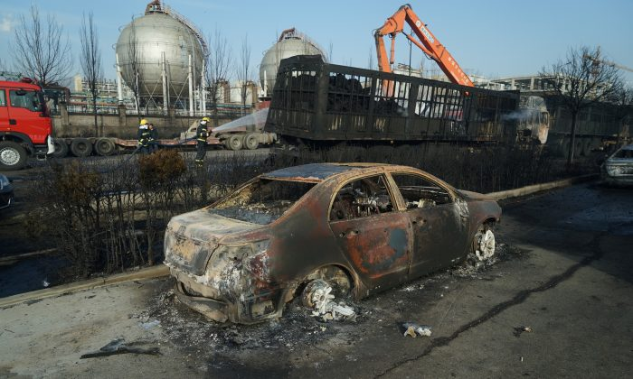 Firefighters work next to burnt trucks and car following a blast near the Shenghua chemical plant in Zhangjiakou, Hebei Province, China on Nov. 28, 2018. (Reuters)