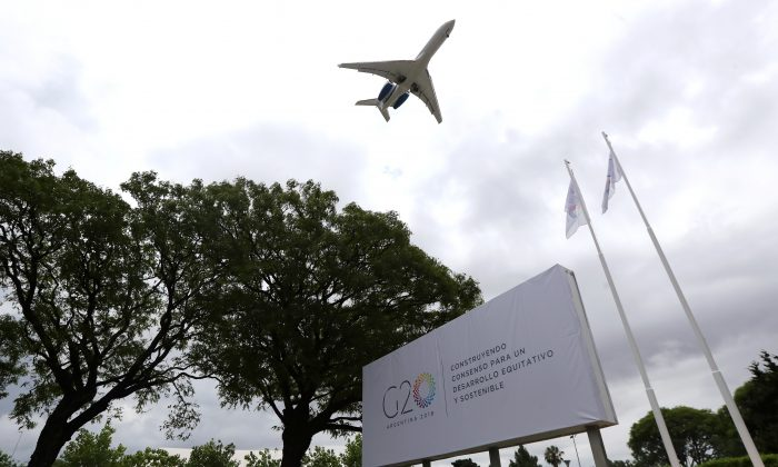 A plane flies over a G20 Summit banner at the Summit's International Media Center in Buenos Aires, Argentina November 29, 2018.  (Marcos Brindicci/Reuters)