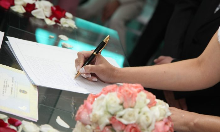 A bride's hand signs wedding documentation in this stock image. (Pixabay)