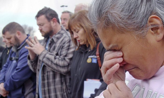 Venus Walker, of Warren, Ohio and a GM employee with 12 years at the Lordstown plant, prays during a vigil outside the Lordstown GM plant, on Nov. 29, 2018. (William D. Lewis/The Vindicator via AP)