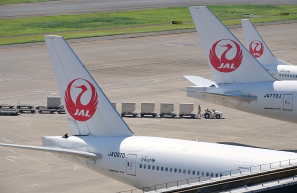 An airport employee works under passenger planes of Japan Airlines at Tokyo's Haneda airport on July 31, 2018.  (Photo by Kazuhiro NOGI / AFP)        (Photo credit should read KAZUHIRO NOGI/AFP/Getty Images)