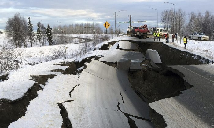 A tow truck holds a car that was pulled from on an off-ramp that collapsed during a morning earthquake in Anchorage, Alaska, on Nov. 30, 2018. (Mike Dinneen/AP)