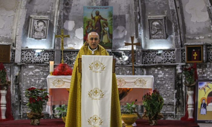An Iraqi Syriac Catholic priest leads Christmas morning mass at the Mar Behnam and Mart Sarah Syriac Catholic Church, which was damaged and defaced during its occupation by Islamic State (IS) group fighters, in the predominantly Iraqi Christian town of Qaraqosh, in Niniveh province some 30 kilometres from Mosul, on Dec. 25, 2018. (Ahmad Al-Rubaye/AFP/Getty Images)