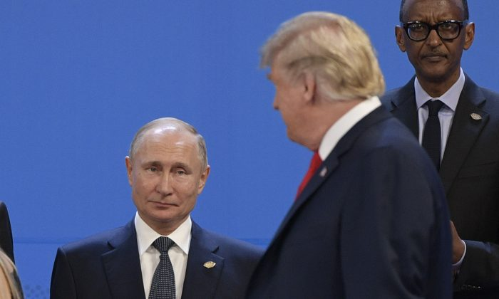 President Donald Trump (R), looks at Russia's President Vladimir Putin as they take place for a family photo, during the G20 Leaders' Summit in Buenos Aires, on Nov. 30, 2018. (Juan Mabromata/AFP/Getty Images)