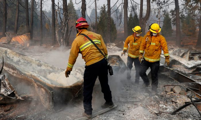 Firefighters move debris while recovering human remains from a trailer home destroyed by the Camp Fire in Paradise, California, on Nov. 17, 2018. (Terray Sylvester/Reuters)