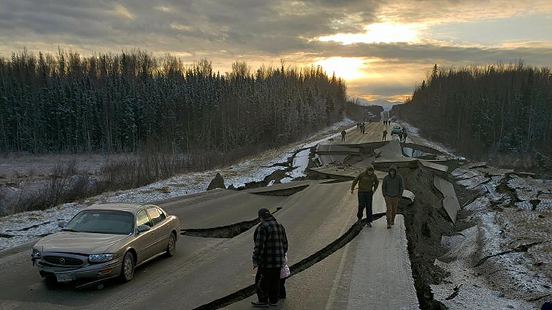 People walk along Vine Road in Wasilla, Alaska