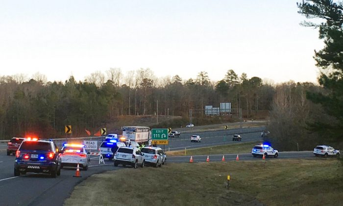 Emergency vehicles are parked along Interstate 30 near the scene where a charter bus that was carrying a youth football team from Tennessee crashed near Benton, Ark., early Monday, Dec. 3, 2018. The bus was carrying the team from Texas to Memphis, Tenn. (Josh Snyder/The Arkansas Democrat-Gazette via AP)