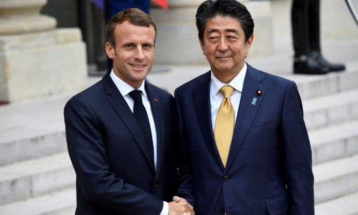 French President Emmanuel Macron (L) shakes hands with Japanese Prime Minister Shinzo Abe (R) after a meeting at the Elysee Palace in Paris on Oct. 17, 2018. ( Bertrand Guay/AFP/Getty Images)
