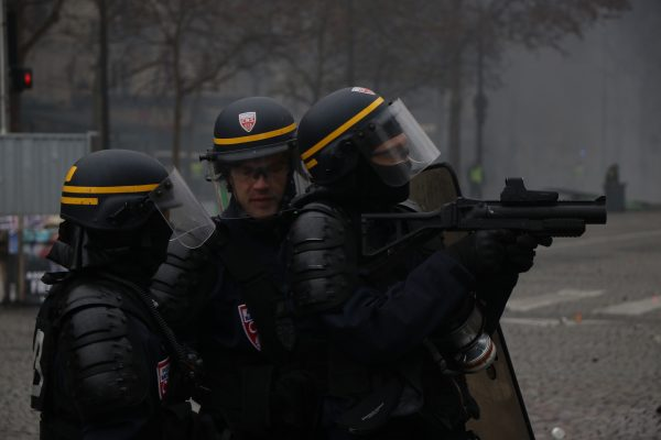 Riot police stand ready to launch grenade gas on Kleber Avenue in Paris.