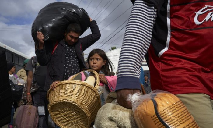 Brittany Rios, of Honduras, center, carries stuffed animals in a wicker basket as her family leaves a shelter for members of the Central American migrant caravan in Tijuana, Mexico, on Nov. 30, 2018. (AP Photo/Gregory Bull)