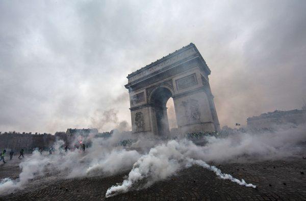 Teargas surrounds riot police near the Arc de Triomphe