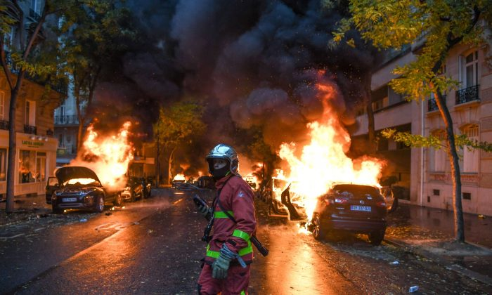 """A firefighter looks on as cars are burning during a """"yellow vest"""" protest in Paris, on Dec. 1, 2018. (Alain Jocard/AFP/Getty Images)"""