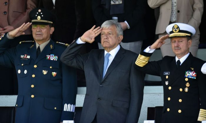 Mexico's President Andres Manuel Lopez Obrador (C) salutes flanked by the Secretary General of Defense Luis Cresencio Sandoval (L) and General of the Navy Jose Rafael Ojeda Duran during the first military ceremony, in Mexico City on Dec. 02, 2018. (Rodrigo Arangua/AFP/Getty Images)