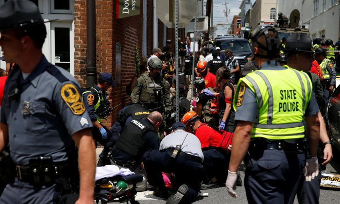 "Rescue workers assist people who were injured when a car drove through a group of counter protestors at the ""Unite the Right"" rally Charlottesville, Va., on Aug. 12, 2017. (Joshua Roberts/Reuters)"