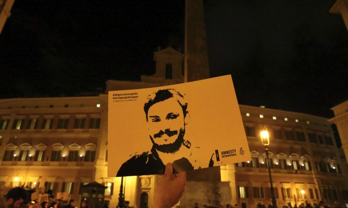 A man holds a placard during a vigil to commemorate Giulio Regeni, who was found murdered in Cairo, in downtown Rome on Jan. 25, 2017. (Reuters/Alessandro Bianchi)