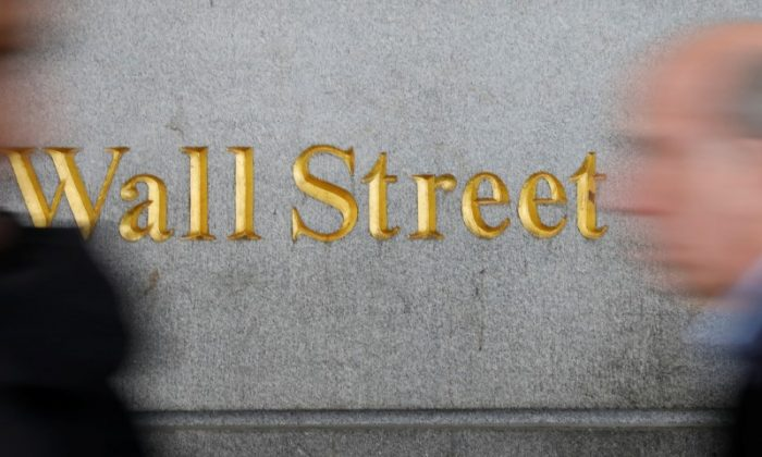People walk by a Wall Street sign close to the New York Stock Exchange (NYSE) in New York, U.S., April 2, 2018. REUTERS/Shannon Stapleton