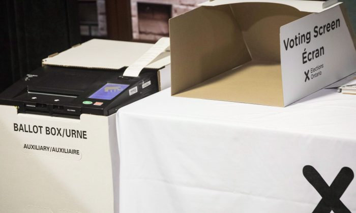 A vote tabulator (L) sits next to a voting screen in Toronto, on May 9, 2018. (The Canadian Press/Chris Young)