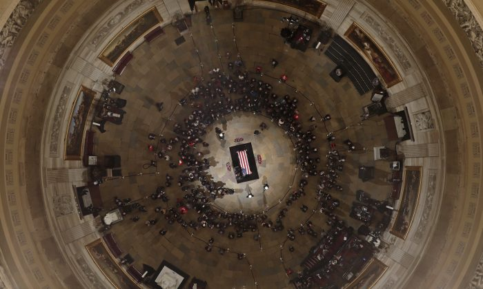 Members of the Bush family gather near the casket of Former President George H. W. Bush as he lies in state in the U.S. Capitol Rotunda in Washington DC, Dec. 4, 2018. (AP Photo/Morry Gash, Pool)