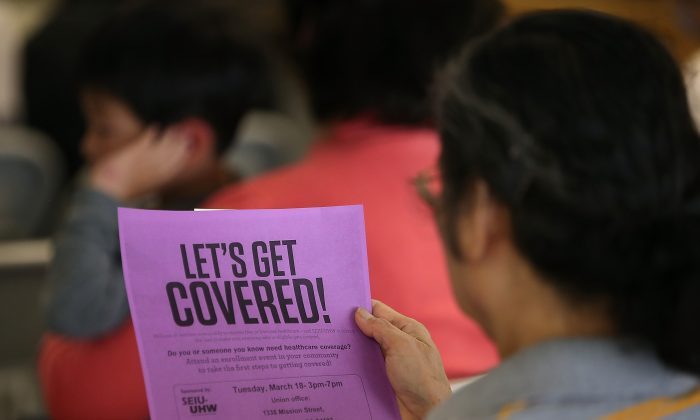 An attendee reads a flyer during a healthcare enrollment fair at the office of SEIU-United Healthcare Workers West in San Francisco, Calif., on March 18, 2014. (Justin Sullivan/Getty Images)