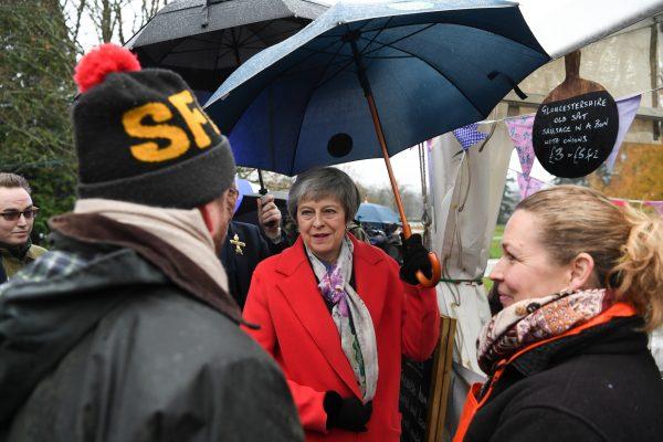 Theresa May shelters under umbrella