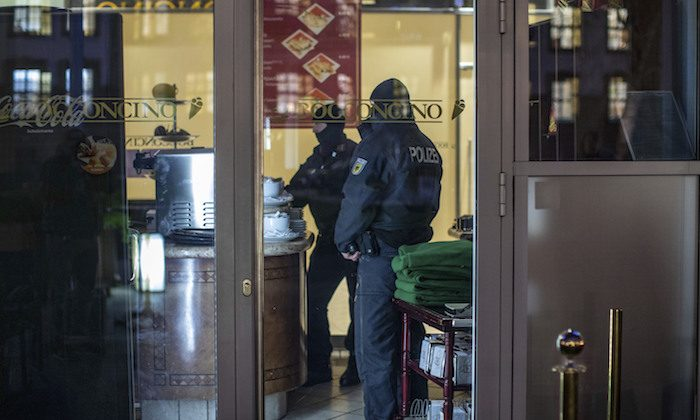 Masked police stand in an ice parlor in Duisburg, western Germany, Wednesday, Dec. 5, 2018 as authorities conduct coordinated raids in Germany, Italy, Belgium and the Netherlands in a crackdown on the Italian mafia. (Christoph Reichwein/dpa via AP)