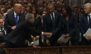 Video: George W. Bush Appears to Give Michelle Obama Candy During Funeral