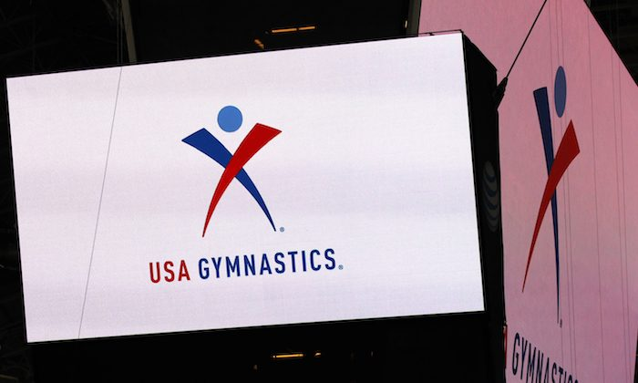 The USA Gymnastics logo is displayed at AT&T Stadium during an news conference announcing in Arlington, Texas. On Dec. 5, 2018. (Ron Jenkins/Star-Telegram via AP)
