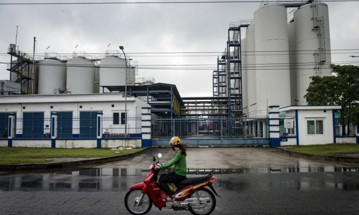 A Vietnamese woman drives a motorbike past a factory in an industrial zone in the central Vietnamese city of Danang on Nov. 10, 2017. (Lillian Suwanrumpha/AFP/Getty Images)