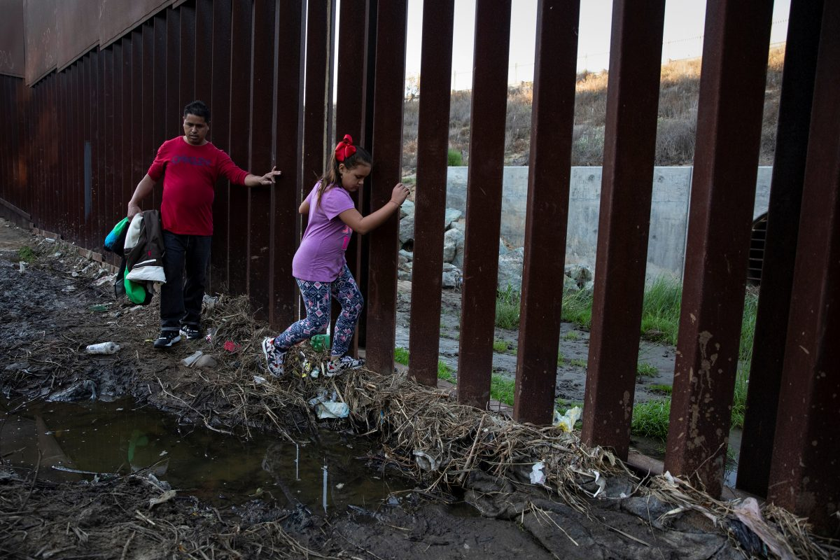 Tony Mauricio Arita and his daughter Andrea Nicole, from Honduras, part of a caravan of thousands from Central America trying to reach the United States, move next to a border wall before crossing illegally from Mexico to the U.S, in Tijuana