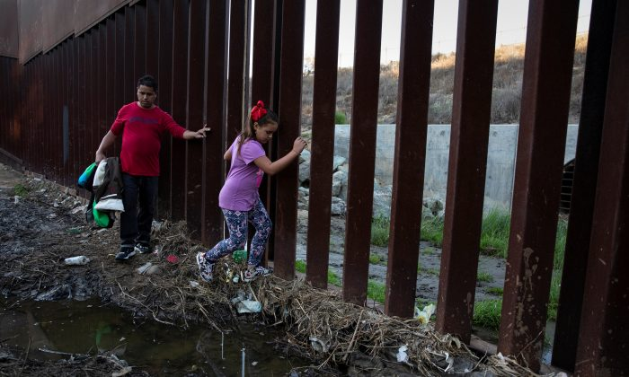 Tony Mauricio Arita, 33 and his daughter Andrea Nicole, 10, from Honduras, part of a caravan of thousands from Central America trying to reach the United States, move next to a border wall before crossing illegally from Mexico to the U.S, in Tijuana, Mexico, on Dec. 4, 2018. (Alkis Konstantinidis/Reuters)