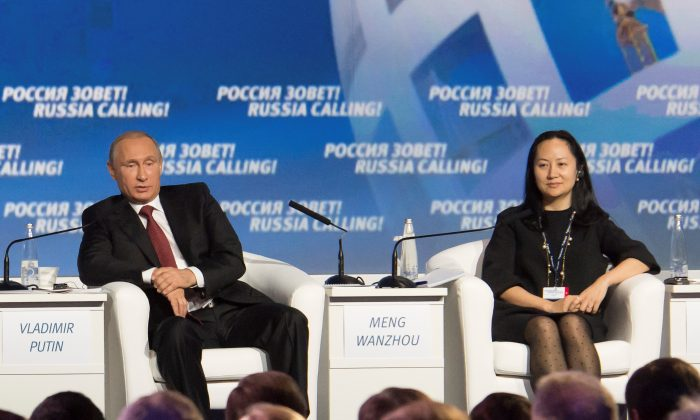 "Russia's President Vladimir Putin (L) and Meng Wanzhou, Executive Board Director of the Chinese technology giant Huawei, attend a session of the VTB Capital Investment Forum ""Russia Calling!"" in Moscow on Oct. 2, 2014. (Alexander Bibik/Reuters)"