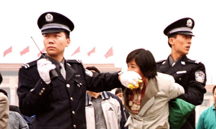 Two Chinese police officers arrest a female Falun Gong practitioner at Tiananmen Sqaure in Beijing on Jan. 10, 2000. The persecution of Falun Gong has continued for nearly 19 years. (Chien-Min Chung/AP Photo)