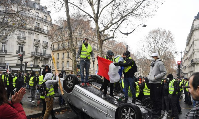 Demonstrators stand on a destroyed car during a protest of yellow vests against rising oil prices and living costs, near the Champs Elysees in Paris, on December 1, 2018. - (Alain Jocard/AFP/Getty Images)