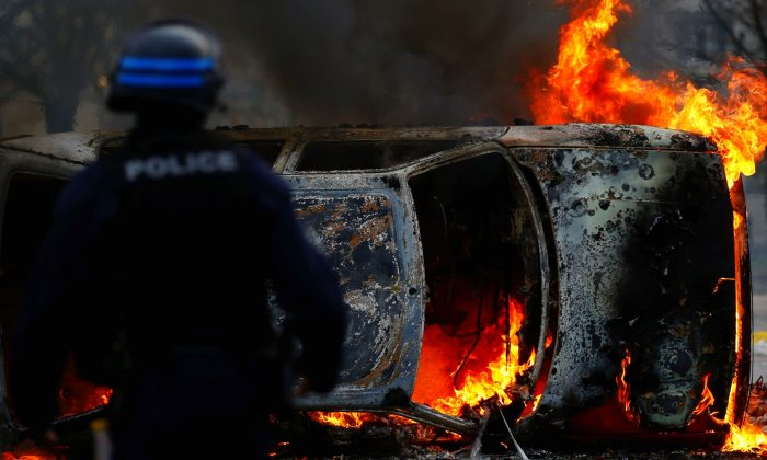 A French riot policeman stands next to a burning car as youth and high school students protest against the French government's reform plan, in Nantes, France, on Dec. 6, 2018. (Stephane Mahe/Reuters)