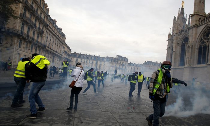 "Protesters wearing yellow vests walk through tear gas during clashes with police at a demonstration of the ""yellow vests"" movement in Bordeaux, France, on Dec. 8, 2018.  (REUTERS/Regis Duvignau)"