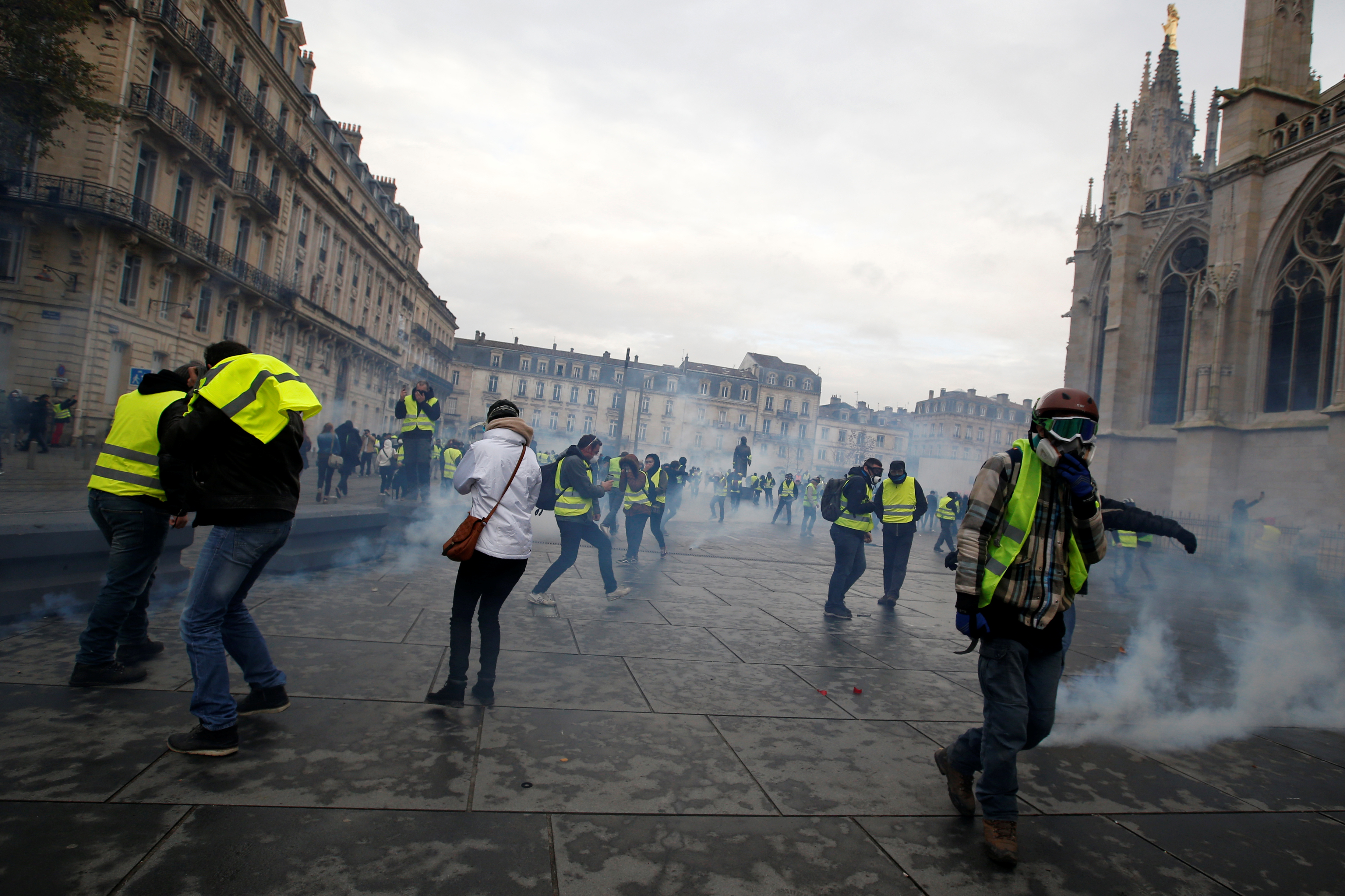 Protesters wearing yellow vests walk through tear gas