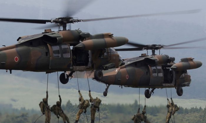 Japanese Ground Self-Defense Force soldiers rappel from UH-60 Black Hawk helicopters during an annual training session near Mount Fuji at Higashifuji training field in Gotemba, west of Tokyo, Japan, on Aug. 24, 2017. (Issei Kato/Reuters)