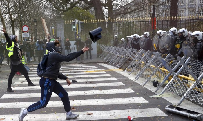 A protestor throws an object at a police line during a demonstration in Brussels on Dec. 8, 2018. (AP Photo/Francisco Seco)