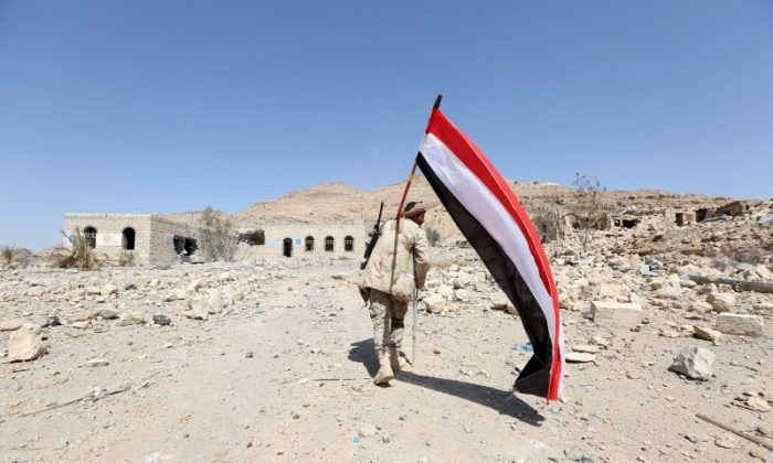 A pro-government army soldier carries Yemen's national flag as he walks at the strategic Fardhat Nahm military camp, around 60km (40 miles) from Yemen's capital Sanaa, Feb. 11, 2016. (Reuters/Ali Owidha/File Photo)