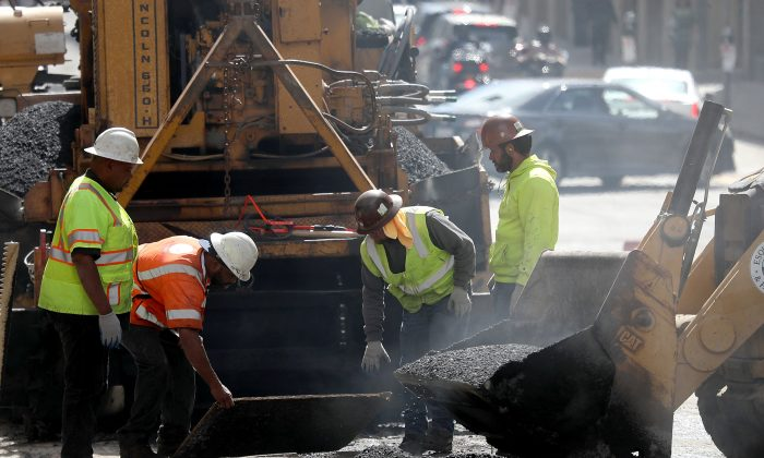 Construction workers smooth tar as they pave a road in San Francisco, Calif., on Oct. 5, 2018. (Justin Sullivan/Getty Images)