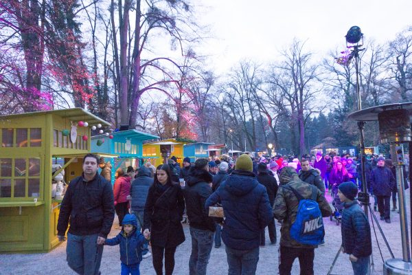 Crowds walk among trees and Christmas market stands at Advent in Maksimir Park Zagreb