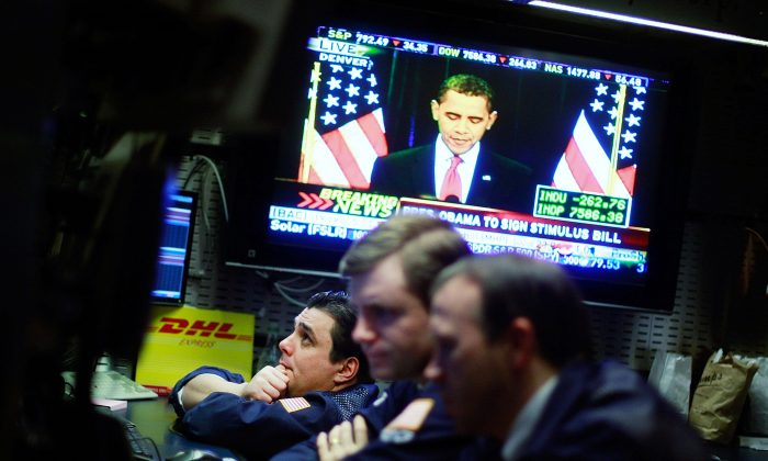 """Traders work on the floor of the New York Stock Exchange during afternoon trading as President Barack Obama is seen on television at the economic stimulus bill signing ceremony on Feb. 17, 2009. Despite evidence that stimulus plans do not stimulate the economy, """"experts"""" continue to recommend them. (Mario Tama/Getty Images)"""