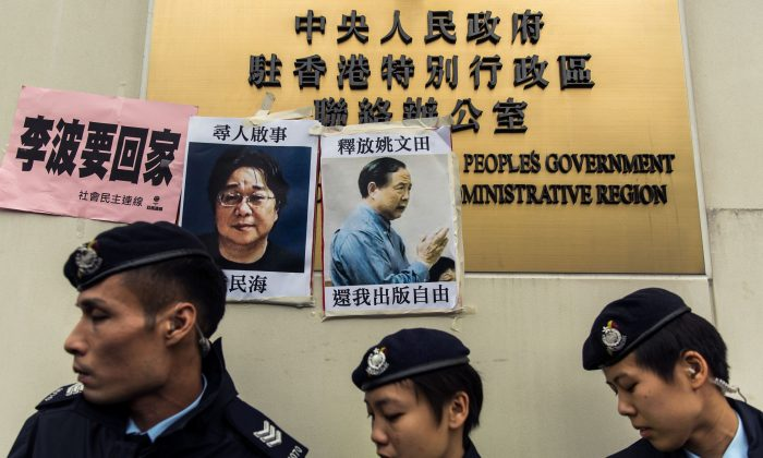 Police walk past missing person notices of Gui Minhai (L), one of five missing booksellers from the Mighty Current publishing house, and Yau Wentian (R), a Hong Kong publisher who was last year jailed for 10 years while preparing to release a book critical of Chinese leadership, posted on top of the sign of China's Liaison Office in Hong Kong on Jan. 3, 2016. (ANTHONY WALLACE/AFP/Getty Images)