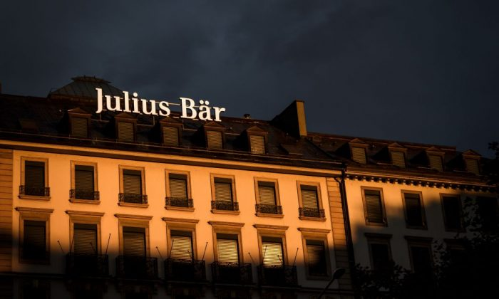 A sign of Swiss private bank Julius Baer is seen on the top of a building at sunset on Sept. 30, 2018 in Geneva. (Fabrice Coffrini/AFP/Getty Images)