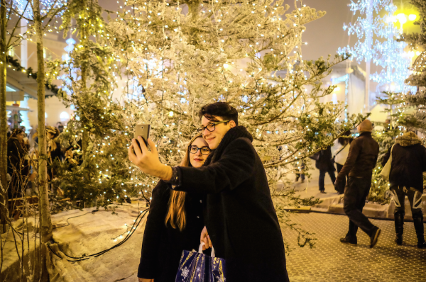 Young couple takes selfie in Christmas square with snow