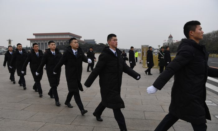 Security personnel patrol in Tiananmen Square ahead of a vote on constitutional amendments at the National People's Congress in Beijing on March 11, 2018.