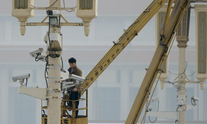 A man checks surveillance cameras on Tiananamen Square in Beijing on Oct. 31, 2013. (Ed Jones/AFP/Getty Images)